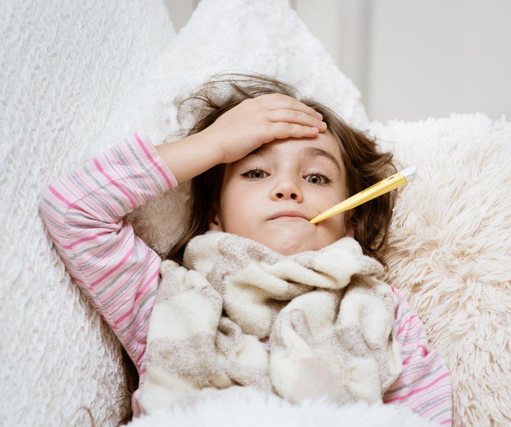 Chore dziecko leży z termometrm, kiedy mama pracuje zdalnie