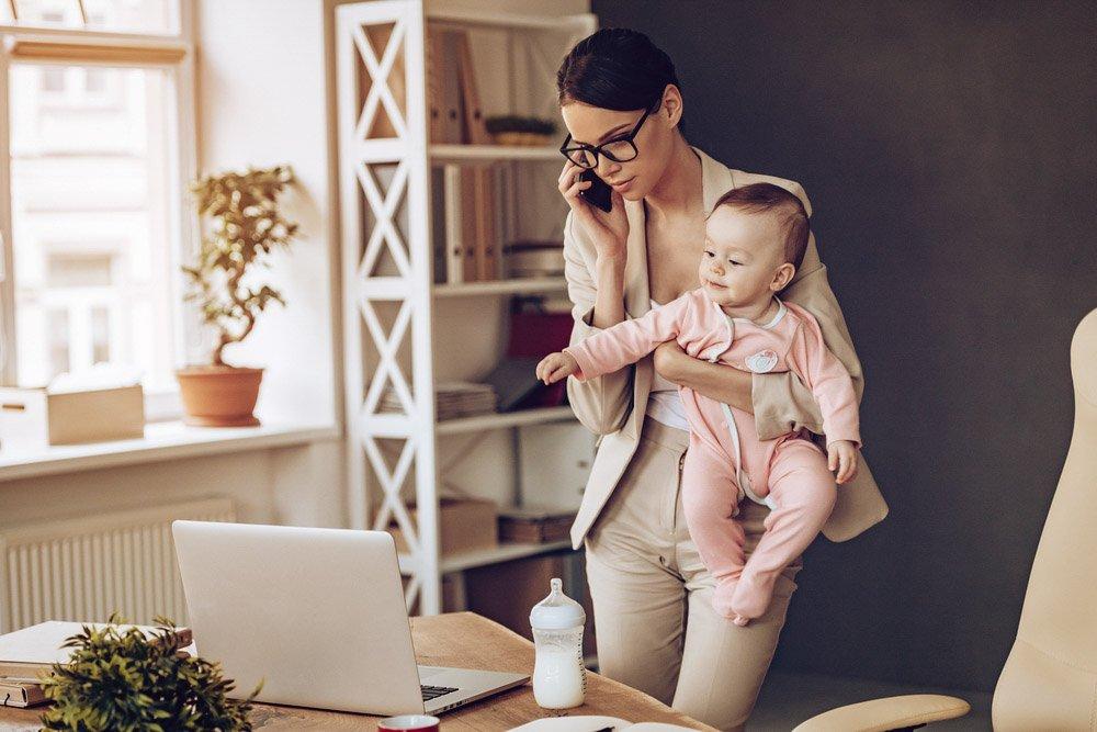 Mama pracuje zdalnie z dzieckiem na rękach